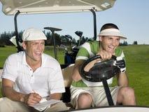 Golfspieler, die im Golfmobil sitzen Lizenzfreies Stockfoto