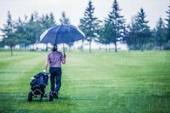 Golfspieler an einem regnerischen Tag den Golfplatz verlassend Stockfotografie