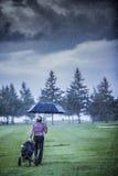 Golfspieler an einem regnerischen Tag den Golfplatz verlassend Lizenzfreies Stockfoto
