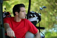 Golfspieler im Buggy. Stockbild