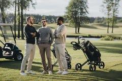 Golfspieler mit den Golfclubs, die zusammen Zeit auf Golfplatz sprechen und verbringen lizenzfreie stockbilder