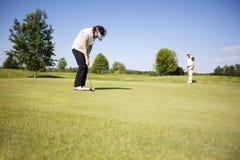 Golfspieler mit zwei Älteren auf Grün. Stockbilder