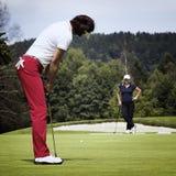 Golfspieler mit zwei Frauen auf Grün Lizenzfreie Stockfotos