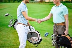 Golfspieler rütteln Hände mit einander lizenzfreies stockfoto