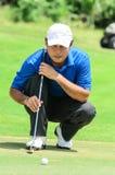 Golfspieler seinen Gang schwingend und geschlagen dem Golfball Lizenzfreie Stockfotos