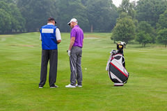 Golfspieler und Transportgestell, die einen Kursführer lesen Stockfoto