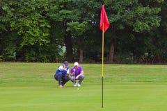 Golfspieler und Transportgestell, welche die Linie des Schlags lesen Stockbild