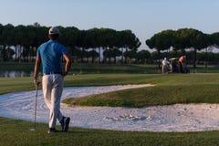 Golfspieler von der Rückseite am Kurs, der zum Loch im Abstand schaut Lizenzfreie Stockfotografie