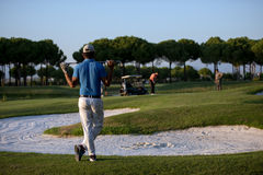 Golfspieler von der Rückseite am Kurs, der zum Loch im Abstand schaut Lizenzfreies Stockfoto