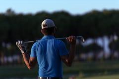 Golfspieler von der Rückseite am Kurs, der zum Loch im Abstand schaut Lizenzfreie Stockbilder