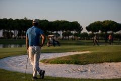 Golfspieler von der Rückseite am Kurs, der zum Loch im Abstand schaut Stockbild