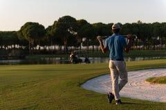 Golfspieler von der Rückseite am Kurs, der zum Loch im Abstand schaut Stockbilder