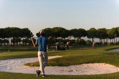 Golfspieler von der Rückseite am Kurs, der zum Loch im Abstand schaut Lizenzfreie Stockfotos