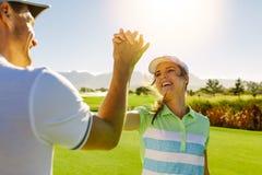 Golfspielergeben hoch--fünf am Golfplatz lizenzfreies stockbild