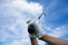 Golfspielerhände in den Handschuhen, die Eisen halten stockfoto
