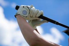 Golfspielerhände in den Handschuhen, die Eisen halten stockfotografie