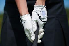 Golfspielerhandschuhe halten das Eisen oder den Putter stockbilder