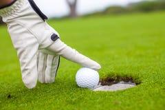 Golfspielermann, der Golfball in das Loch drückt Stockfoto