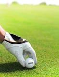 Golfspielermann, der Golfball hält Stockbild