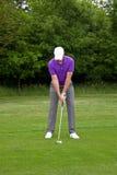Golfspielerposition für einen mittleren Eisenschuß Stockfotos