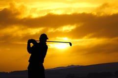 Golfspielersonnenuntergangschalter Stockfoto