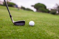 Golfstok en bal op groen gras Stock Foto