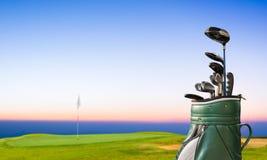 Golfutrustning och golfpåse på gräsplan och hål som bakgrund Royaltyfria Bilder