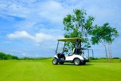 Golfvagn i farled av golfbanan med det nya fältet för grönt gräs arkivfoton