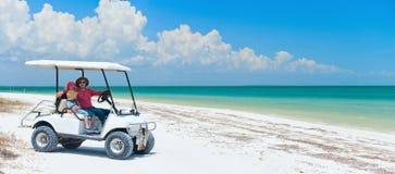 Golfwagen am tropischen Strand Stockfoto