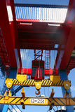 Goliath crane. Red, yellow and blue Goliath crane loading of goods on clear blue sky background Royalty Free Stock Image