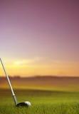 Golpe de la pelota de golf a lo largo del espacio abierto en la puesta del sol Foto de archivo
