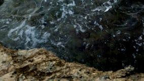 Golpe de las ondas del mar en la orilla de piedra almacen de video