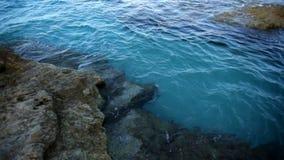 Golpe de las ondas del mar en la orilla de piedra almacen de metraje de vídeo