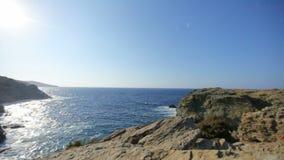 Golpe de las ondas del mar en la orilla de piedra en un día soleado almacen de video