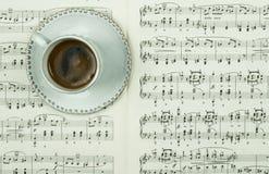 Golpe do café preto no copo e nos pires brancos em notas clássicas impressas da música como o fundo Tempo da pausa imagem de stock royalty free