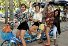 Golpe Saen, Tailândia: Quatro mulheres tailandesas que montam uma bicicleta Imagem de Stock