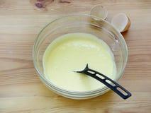 Golpeado en las yemas de huevo de un pollo de la espuma con el azúcar en un bol de vidrio en un fondo de madera Fotos de archivo