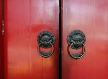 Golpeador de bronce viejo con la puerta roja Foto de archivo libre de regalías