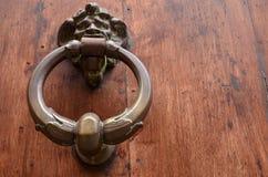 Golpeador de cobre amarillo en la puerta de madera Fotos de archivo libres de regalías