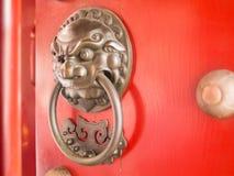Golpeador de puerta chino de la cabeza del león en puerta roja Imágenes de archivo libres de regalías