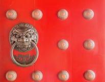 Golpeador de puerta chino de la cabeza del león en puerta roja Foto de archivo libre de regalías