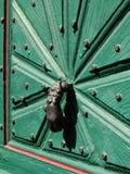 Golpeador de puerta del arrabio en puerta rústica verde de la madera Imágenes de archivo libres de regalías