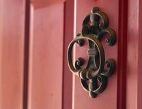 Golpeador de puerta del molde del hierro en puerta roja Imagen de archivo libre de regalías