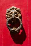 Golpeador de puerta oxidado viejo de la cabeza del león del hierro en una puerta roja Foto de archivo
