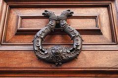 Golpeador viejo del tirador de puerta del metal en fondo de madera Imagenes de archivo