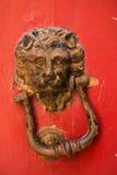 Golpeadores de puerta principales del león en una puerta roja Foto de archivo libre de regalías