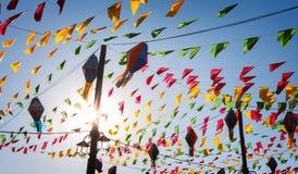 Golpeando, banderas coloridas del partido, en un cielo azul Imagen de archivo libre de regalías