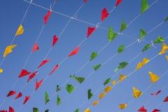 Golpeando, banderas coloridas del partido, en un cielo azul Fotos de archivo
