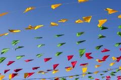 Golpeando, banderas coloridas del partido, en un cielo azul Imagenes de archivo
