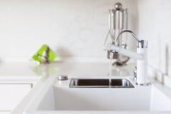 Golpecito de agua moderno del cromo del diseñador sobre el fregadero de cocina blanco fotografía de archivo